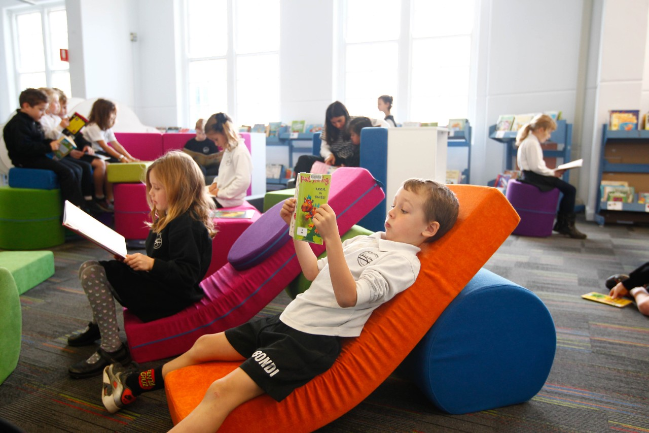 Children reading books in the school library. They are laying on bright coloured cushions