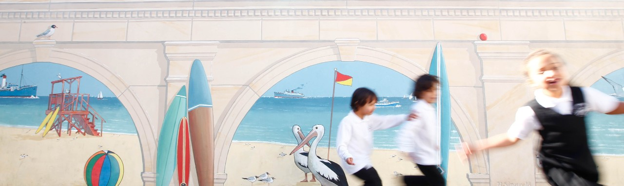 A mural looking through sandstone arches towards a summer day at the beach. Surfboards and beach umbrellas leaning against the archways. Children running and laughing in front of the mural.