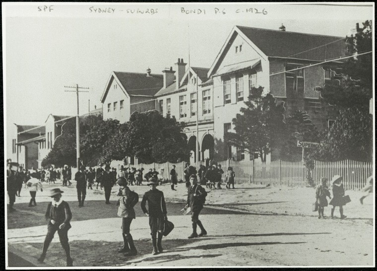 Black and white photo of Bondi Public in 1926. There are a number of school children in uniforms and hats walking across a rocky road away from the front of school.